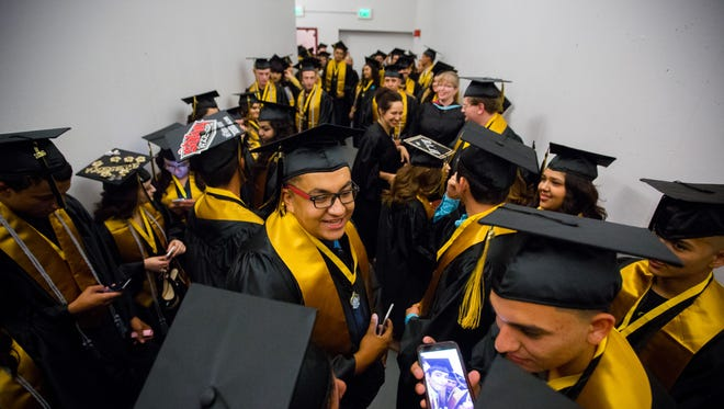 Rio Grande Preparatory Institute graduating Senior Angel Villa, center, talks with friends while waiting in a tunnel at the Pan American Center for the start of the school commencement ceremony, May 18, 2016. The start of the ceremony was delayed 25 minutes due to weather conditions which caused a canopy outside the center to collapse.