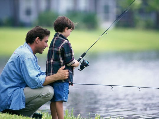 Side profile of a father and his son fishing