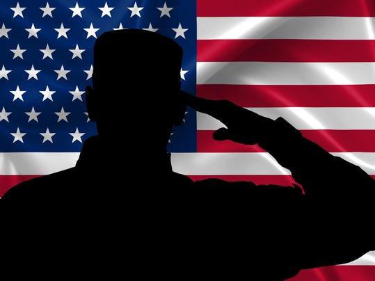 Silhouette of American (USA) soldier saluting to USA flag
