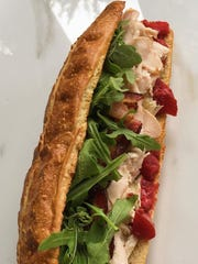 A sandwich created by Nick Capaldi at Marie's Sandwich Bar comprises roasted turkey, roasted red peppers, apple wood smoked bacon, brie, seasonal jam and arugula on a pretzel roll. Capaldi's business pays tribute to his family's long-time involvement in the food industry.