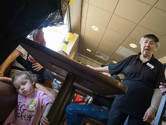 Mary Brooks speaks with friends and co-workers. Her 2-year-old great-granddaughter Brooklyn Cooper explores under a table.