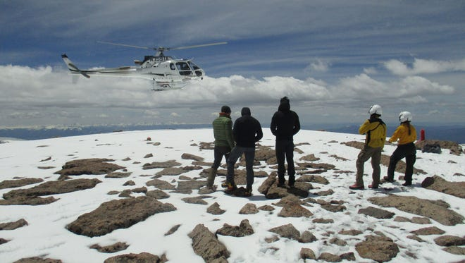 A helicopter hovers near the summit of Longs Peak during evacuation operations to rescue 10 Army soldiers stranded atop the 14,000-foot peak on Friday, June 3, 2016.