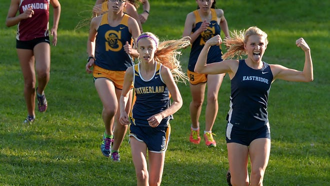 Eastridge's Veronica Wojnowski, right, reacts to the cheers from the boys team as she and Pittsford Sutherland's Rebecca Preisser lead the pack early during a cross country meet held at Mendon Ponds Park on Monday.