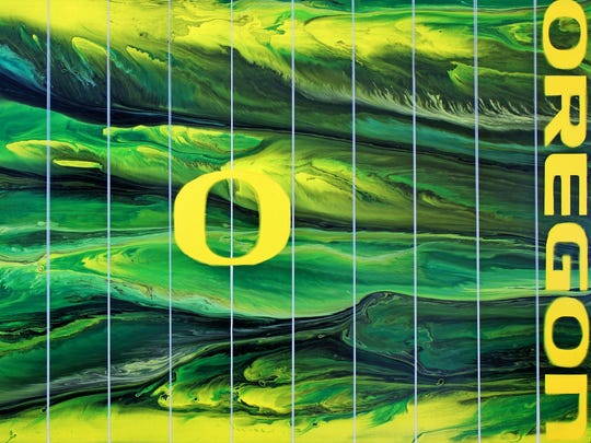 """Oregon Football"" by Eugene artist Michael Cross is a large acrylic painting of Autzen Stadium's field from an overhead perspective. Made with the multiple colors that the Ducks wear in a football season, the piece represents the unstoppable fluidity of the Ducks' high-powered offense."