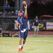 Centennial quarterback Daniel Smith throws the ball to his receiver during the team's game against the Chandler Wolves, Friday, Aug. 29, 2014, in Peoria, Ariz.