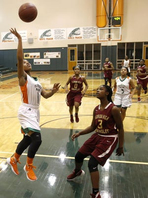 FAMU DRS seventh grader Erin Turral lays the ball up past Florida High's Kyndall Thomas during their game at FAMU DRS last Saturday. Turral scored 21.