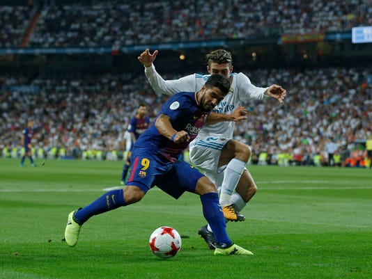 Barcelona's Luis Suarez, left, vies for the ball with Real Madrid's Mateo Kovacic during the Spanish Super Cup second leg soccer match between Real Madrid and Barcelona at the Santiago Bernabeu stadium in Madrid, Wednesday, Aug. 16, 2017. (AP Photo/Francisco Seco)