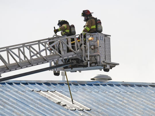 Farmington firefighters vent the roof  Saturday as they battle a structure fire on the 200 block of Pinon Street in Farmington.