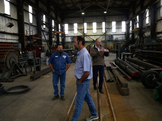 From left, Mining Equipment Inc. Shop Manager Floyd Garcia, and company Vice Presidents Matt Pope and Rob Pope tour their fabrication shop on Nov. 3 in Farmington.