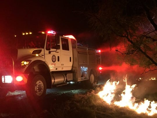 Firefighters battle a wildfire east of Ballinger. The