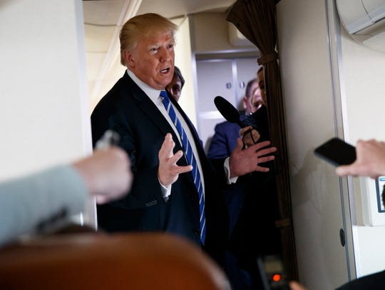 President Trump talks with reporters aboard Air Force