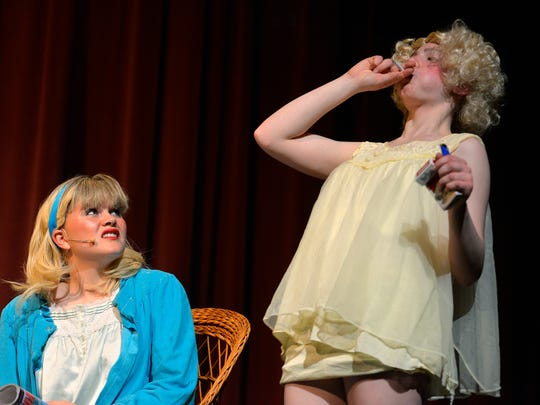 "Sandy (Lauren Davis), left, looks on in disgust as Frenchie (Lillie Kuss) shows her how to French inhale a cigarette during a slumber party with the Pink Ladies on Monday during a rehearsal of ""Grease"" at Rocori High School."