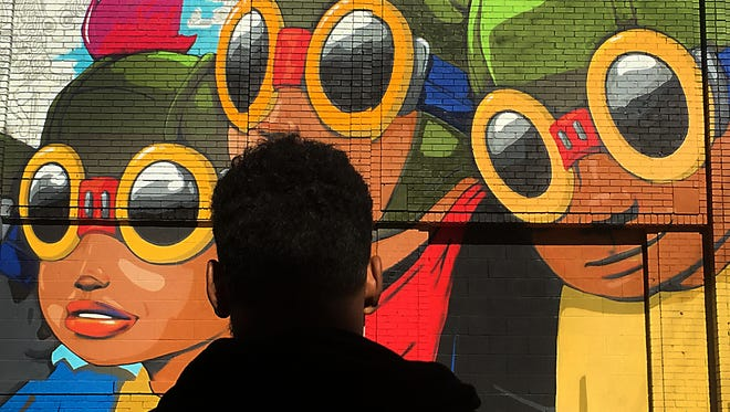 """Chicago-based mixed-media artist Hebru Brantley stands back to look at his just finished mural """"Flyboy"""" in Eastern Market on Thursday, Sept. 24, 2015 in Detroit. Brantley is one of more than 45 local and international artists participating in the Murals in the Market project."""