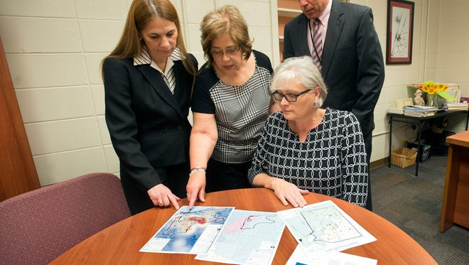 Kathleen Heubach, University of West Florida director, Institute for Innovative Community Learning, seated, meets with Escambia County School District officials, Laura Colo, left, Marcia Nowlin, center and Steve Marcanio, review the maps for the proposed Promise Zone project. The group discovered Monday that its bid was not chosen for Promise Zone designation.