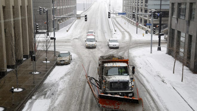 A snow plow moves down Eighth Street during snowfall in February 2014 in Des Moines.