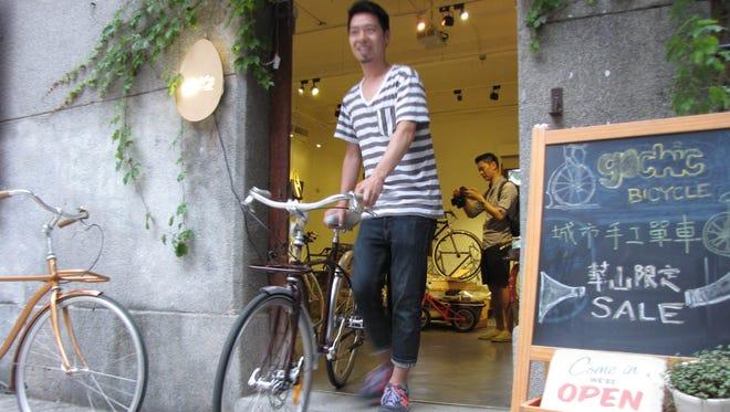Alex Chou, founder of GoChic Bicycle in Taipei, Taiwan, wheels a bike out of his shop in the Huashan art center.