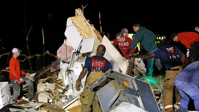 Emergency personnel search the remains of several mobile homes in Louisville, Miss., for survivors early April 29 after a tornado hit the area.