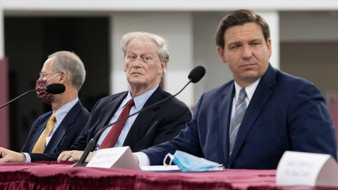 Gov. Ron DeSantis and Florida State University President John Thrasher listen as FSU Head Football Coach Mike Norvell speaks during a collegiate athletics roundtable held by DeSantis at the Albert J. Dunlap Athletic Training Facility on the FSU campus Tuesday, August 11, 2020.