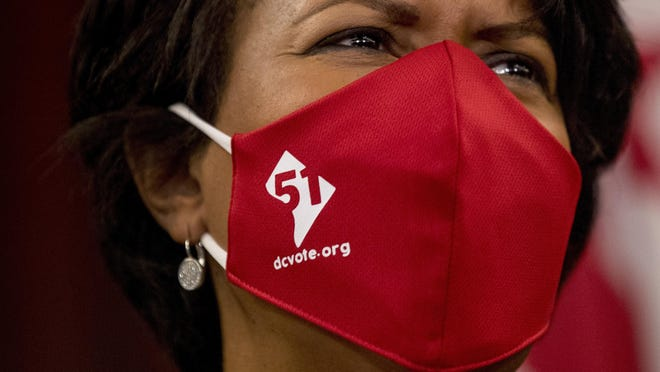 District of Columbia Mayor Muriel Bowser wears a mask with the number 51 over a map of the District of Columbia during a news conference on D.C. statehood.