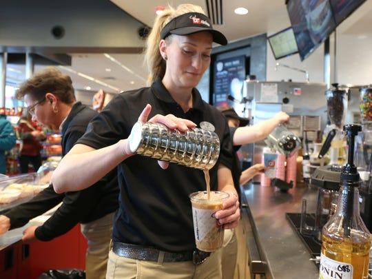 Kari Heinrich of Altoona pours coffee at the new QT Kitchens on East University Avenue in Des Moines.