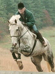 Bob Kinsley jumps Mexican Wave, an Irish Draught Cross, during his weekly outing in 1998.
