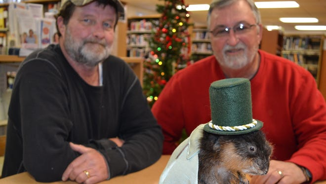 Princess Anne Town Commissioners Joey Gardner, left, and Mike Hall pose with Marshall P. Muskrat, the town's mascot that will dive into 2015 at this year's New Year's Eve street party.