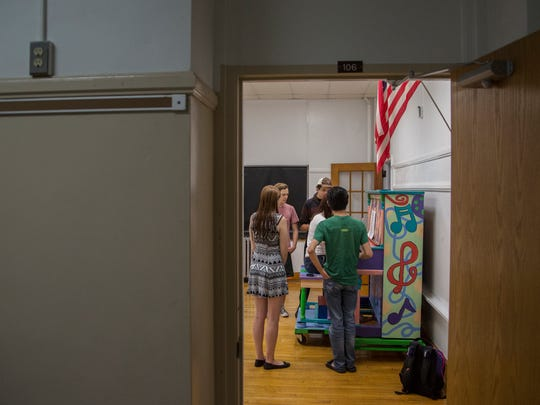 David O'Connell, of Newport, Rhode Island, Parker Wall, of Chicago, Kayti Wiita, of Minnetonka, Minnesota, Jeremy Berdin, of Seattle, Washington and Jennifer Kiefer, of Minnetonka, Minnesota, members of the  Cedar Summerstock Theater gather around a piano in one of the community rooms in the former St. Ansgar elementary school on Friday morning, July 28, 2017, in St. Ansgar.