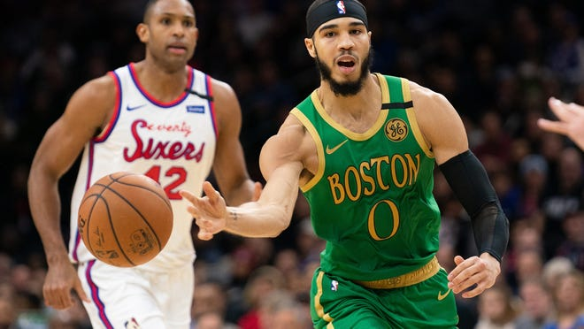 Celtics forward Jayson Tatum passes the ball with 76ers center Al Horford trailing the play during a game in January.