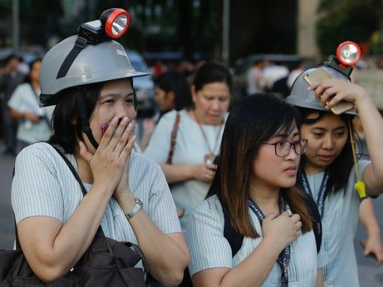 Wearing protective helmets, employees evacuate their