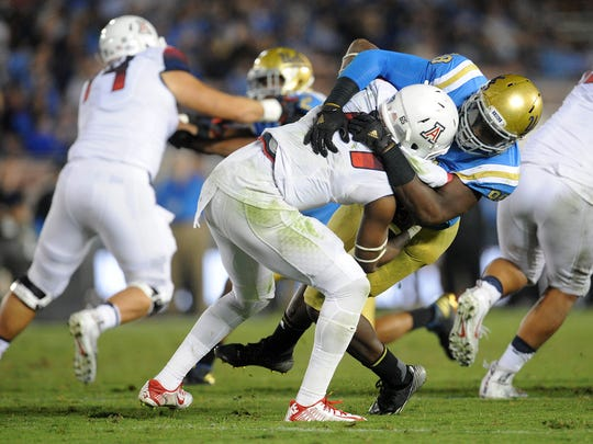 FILE -- UCLA Bruins defensive lineman Takkarist McKinley (98) brings down Arizona Wildcats quarterback Khalil Tate (14) during the second half at Rose Bowl.