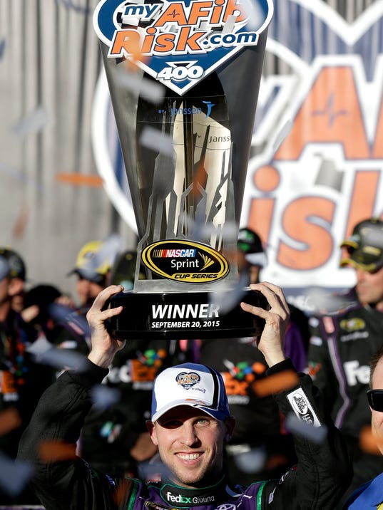 Denny Hamlin celebrates as he holds the trophy in Victory Lane after winning the NASCAR Sprint Cup Series auto race at Chicagoland Speedway, Sunday, Sept. 20, 2015, in Joliet, Ill. (AP Photo/Nam Y. Huh)