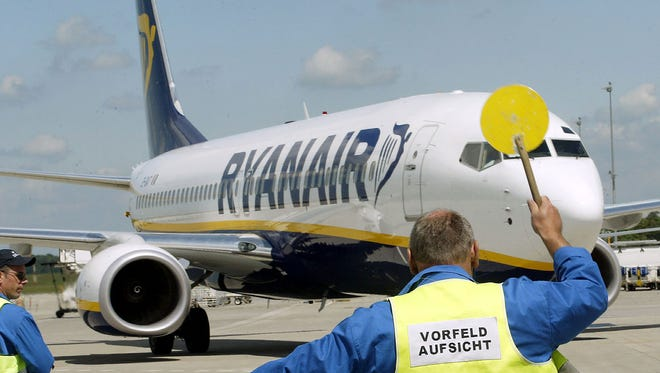 An airport employee signals to a Ryanair jet at Germany's Hahn airport.