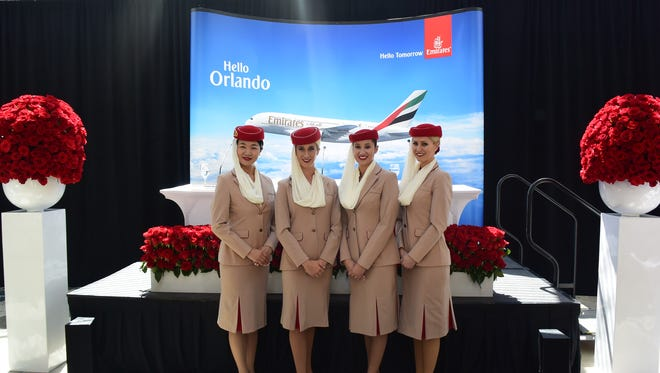 Emirates flight attendants pose for a photo ahead of a celebratory press conference for the airline's inaugural Orlando flight on Sept. 1, 2015.