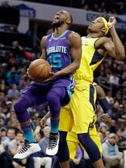 Charlotte Hornets' Kemba Walker (15) is fouled as he drives past Indiana Pacers' Myles Turner during the first half of an NBA basketball game in Charlotte, N.C., Sunday, April 8, 2018.