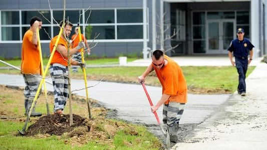Lafayette Parish inmates work on a concrete walkway at the new Lafayette Parish Sheriff's Office Public Safety Complex on Willow Street Monday.