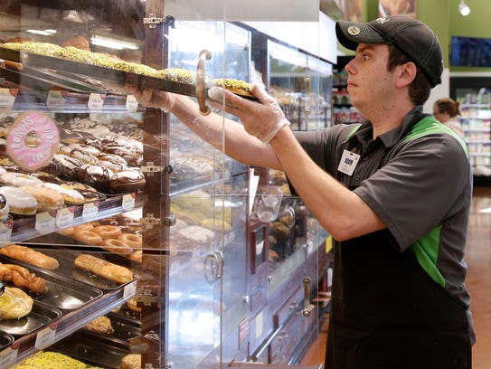 Festival Foods bakery clerk Adam Leitner fills the