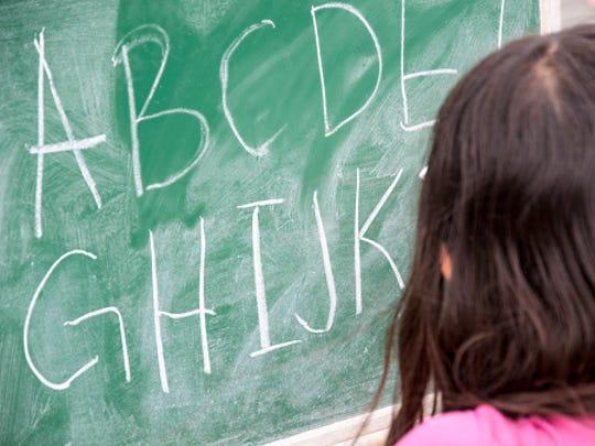 Girl writes alphabet on chalkboard