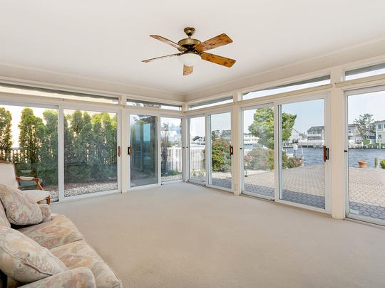 The sunroom features custom windows and views of the water.