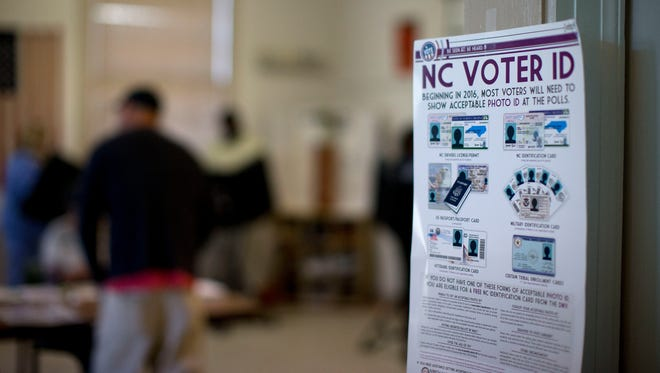 This photo taken March 15, 2016, shows a NC Voter ID rules posted at the door of the voting station at the Alamance Fire Station in Greensboro, N.C. A federal appeals court on Friday blocked a North Carolina law that required voters to produce photo identification and follow other rules disproportionately affecting minorities, finding that the law was intended to make it harder for blacks to vote in the presidential battleground state.