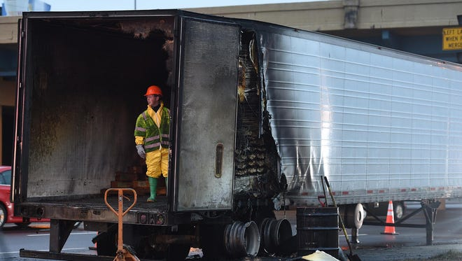 A haz-mat crew from Premier Protective Service, Inc. prepare to unload chicken nuggets from a semi that  caught fire on Tuesday morning Jan. 26, 2016.