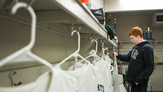 Mount Pleasant boy's basketball team manager Creston Campbell hangs up players' uniforms in the team room on Monday evening.