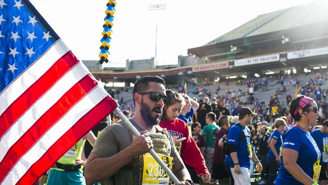 A runner brings the American Flag over the finish line during the 11th Annual Pat's Run Saturday, April 25, 2015 in Tempe. Over 30,000 runners attended Pat's Run last year, breaking the record for the highest attendance during the run's history.