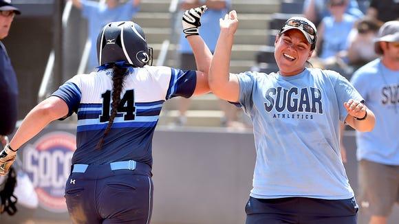Enka softball coach Jennifer Kruk congratulates Addison Harris after her walkoff home run in last month's NCHSAA 3-A championship series played in Greensboro.
