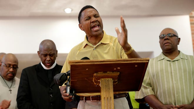 Rev. Terry Webster, of Corinthian Baptist Church and Indianapolis Ten Point Coalition, says a prayer during a press conference at Barnes United Methodist Church on July 8, 2016.