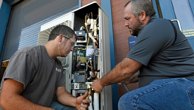 Instructor Ken Boxler, right, works with HVAC student Mason Deshong, 17, on a heat pump Monday, August 30, 2016 at Franklin County Career and Technology Center. The school is increasing enrollment and programs offered to students.