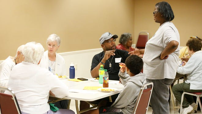 Antonio Godfrey listens to Daisy Frazier at a Humanity Project potluck gathering Saturday, Aug. 13.