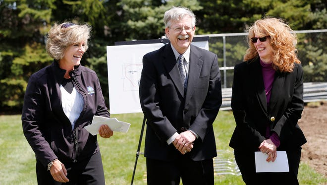 Parks Superintendent Claudine Laufman, left, reacts after Bill and Michele McCaw surprised her with a check for $107,000 for phases II and III for a new playground Wednesday, March 29, 2017, at McCaw Park in Lafayette. The three, along with other local officials, were on hand for groundbreaking for phase I of the new playground, which was made possible by a $126,000 grant from the McAllister Foundation.