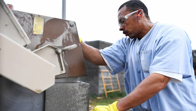 Tennessee Department of Corrections inmate Robert Rucker uses a masonry saw to cut cinder blocks for the new West Tennessee Regional Training Center.