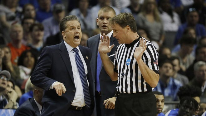 FILE - In this March 26, 2017, file photo, Kentucky head coach John Calipari argues a call with referee John Higgins in the first half of the South Regional final game against North Carolina in the NCAA college basketball tournament in Memphis, Tenn. Referee John Higgins of Omaha has contacted law enforcement to report he's received death threats after Kentucky's loss to North Carolina in the NCAA South Regional final. A person with knowledge of the situation told The Associated Press that Higgins reported threats on his home phone, which has an unlisted number, and on the office phone for his roofing company. The person requested anonymity because the investigation is ongoing. (AP Photo/Mark Humphrey, File)