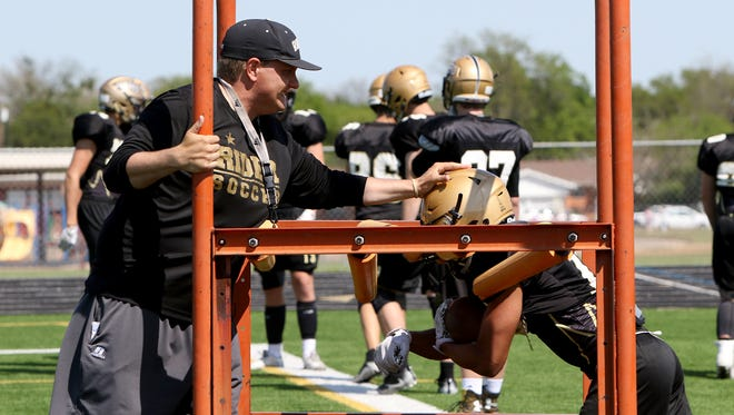 Rider head football coach Marc Bindel runs his team though drills during spring practice Tuesday, April 24, 2018, at Rider High School.